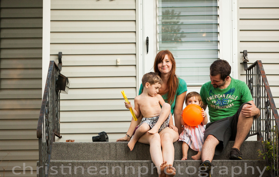 Duluth MN Lifestyle Family Session with a beloved teddy bear, apple tree, apples, sleepy kids, balloons, lawnmower, siblings, diaper, laundry, mom, dad - all outdoors in the back yard of their home.