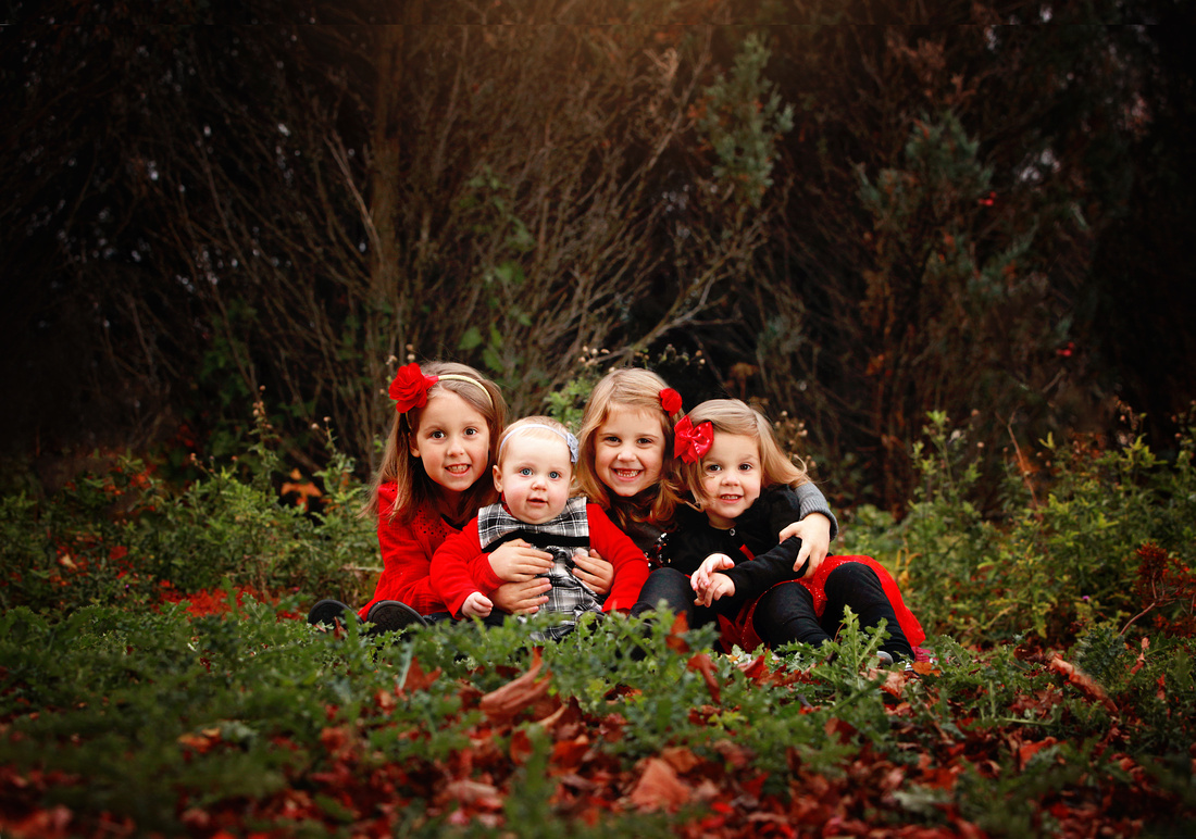Four girl sisters at Leif Erickson Park in the fall wearing red and black colors
