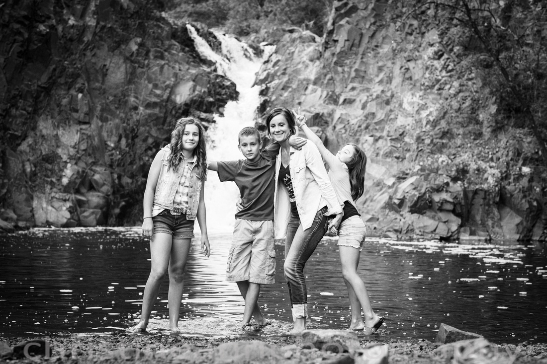 Family photograph in front of waterfall with tweens and teens in Duluth MN at Lester Park.