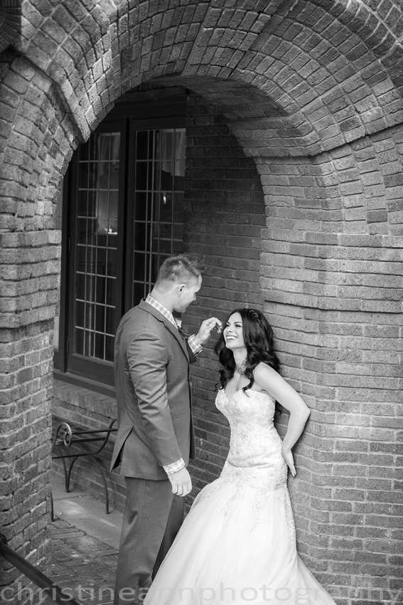 Bride and groom portraits, laughing on brick wall